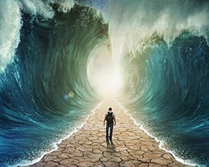 A man walking through the water with the waves parted.